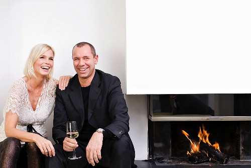 A couple sitting next to a fireplace drinking wine