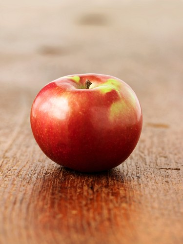 A red apple on a wooden surface