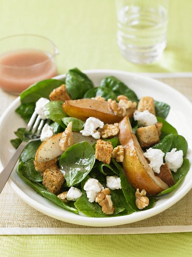 Spinach Salad with Pear Slices, Walnuts and Feta Cheese on a Plate with Fork