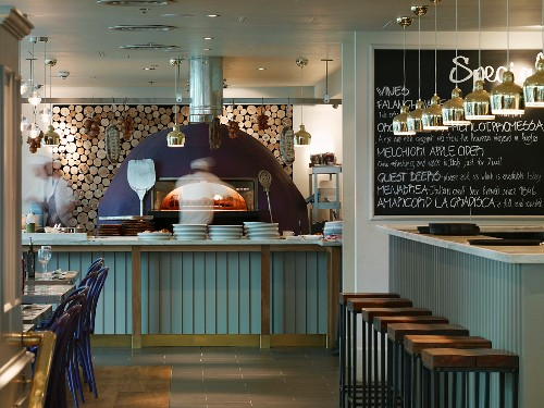 Restaurant in London with modern pizza oven in front of wood stack and bar with pendant lights in front of specials board