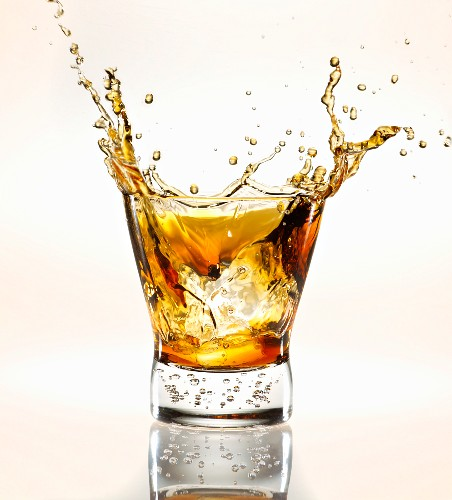 Ice Cube Splashing into a Glass of Scotch; White Background