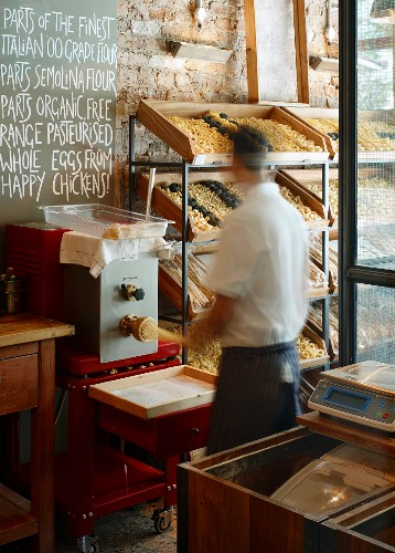 Rack of hand-made pasta and man in action at the pasta machine beneath blackboard with hand-written text