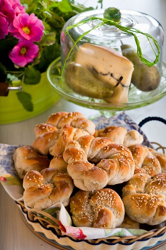 Plaited sesame rolls in front of cheese cover with blue cheese and pears