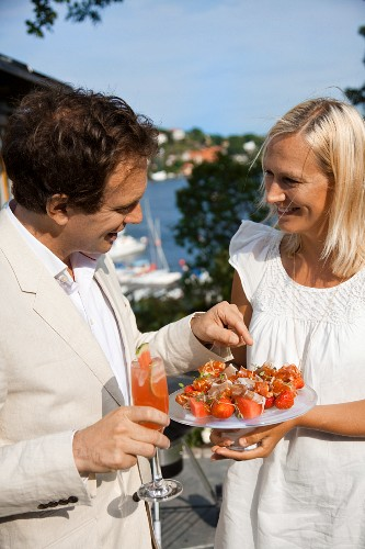 Couple with fruit skewers and a melon drink at a summer party