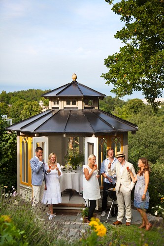 Three couples with drinks in front of garden pavilion