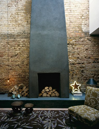 Armchair & rug in front of fireplace on brick wall