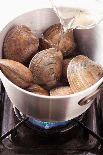 Pour white wine onto clams