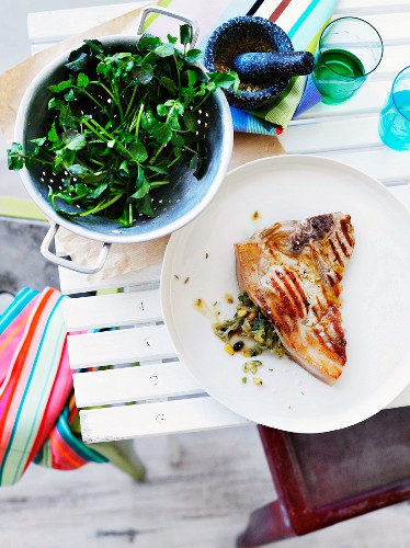 Grilled pork cutlet stuffed with olive pesto with watercress salad