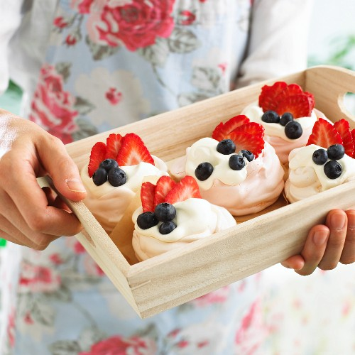A person holding a wooden tray of meringue nests
