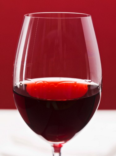 A glass of red wine with wine legs (clue as to the alcohol content)