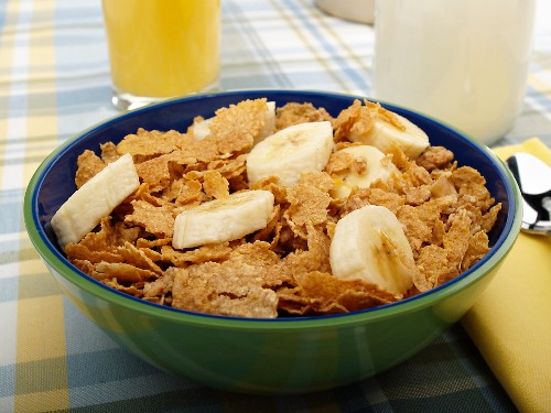 Bowl of Wheat Flake Cereal with Banana Slices; Glass of Milk and Orange Juice