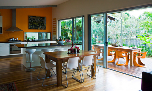 A view from an open-plan living room onto a spacious garden terrace with modern plastic chairs and a long wooden table