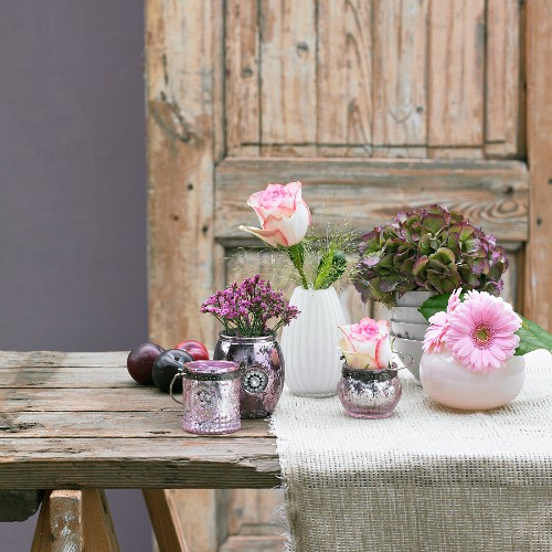 Summery table decorations consisting of vases of flowers and plums