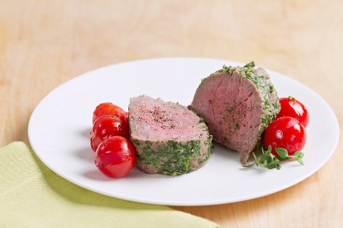 Steamed veal fillet with a herb coating and cherry tomatoes