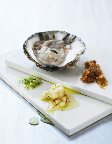 An oyster with various salsas