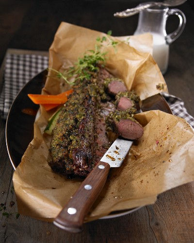 Saddle of hare with vegetables on baking paper