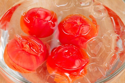 Tomatoes being quenched in iced water