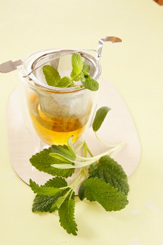 A glass of herb tea and a tea strainer