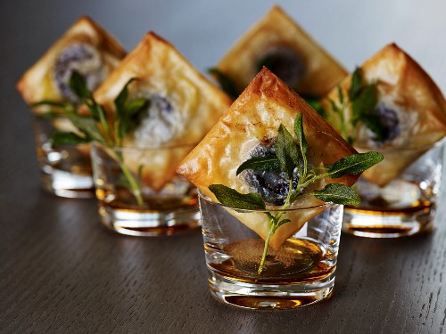 An aperitif accompanied by black pudding canapes and crispy sage