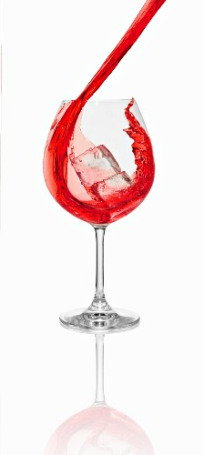 A red cocktail being poured into a glass with an ice cube