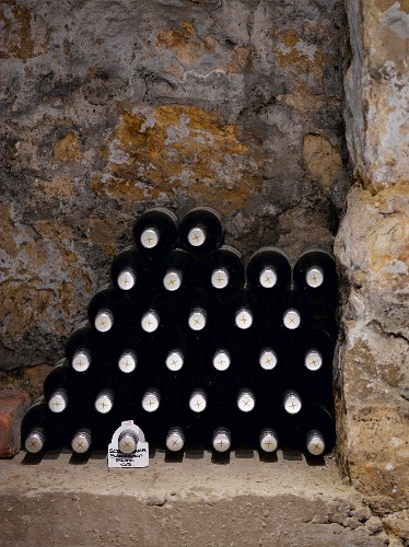 A stack of wine bottles in a niche in a wall