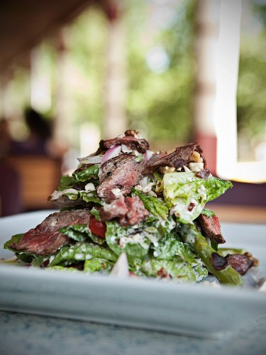 Sliced Sirloin Steak Over a Salad of Romaine Lettuce, Grape Tomatoes, Walnuts, Asparagus and Blue Cheese Dressing