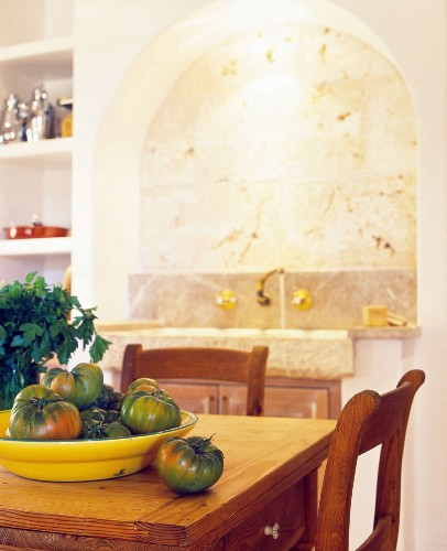 Yellow dish of tomatoes on rustic table in front of niche with rounded arch and integrated sink