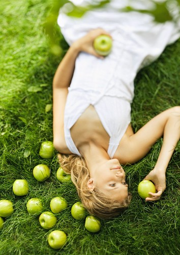Young woman lying in grass, holding apples