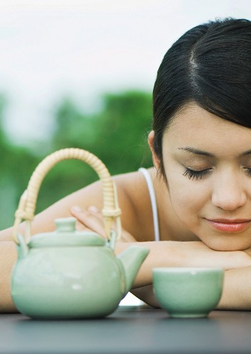 Woman resting head on arms near tea service