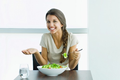 Teen girl eating salad, holding up hand and shrugging shoulders