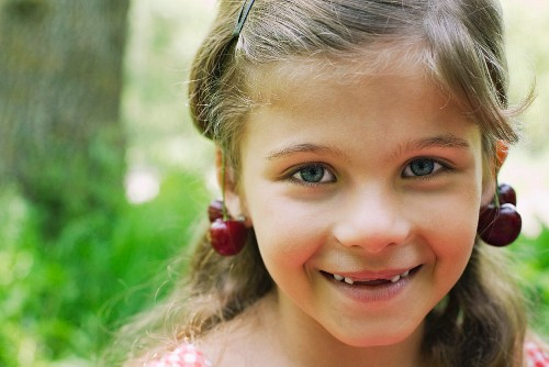 Girl with cherries dangling from her ears, portrait