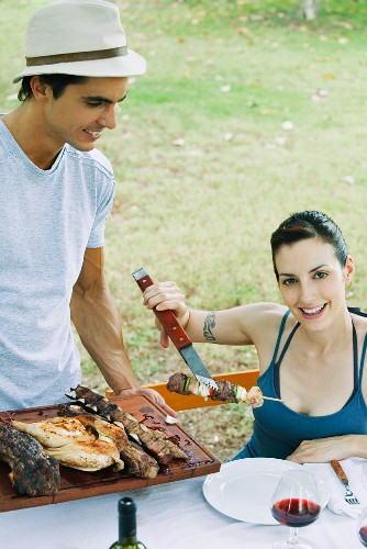 Woman taking kebab from tray of grilled meats, smiling at camera