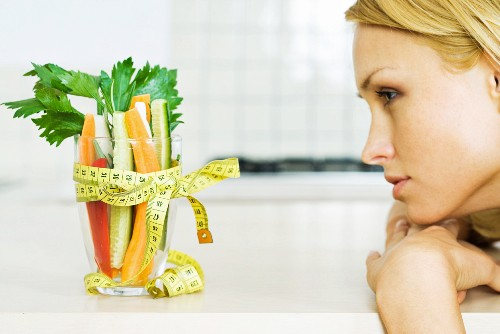 Young woman looking at glass full of vegetables with a measuring tape bow, profile