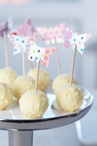Paper butterflies attached to toothpicks with masking tape as a way to serve for white chocolate truffles
