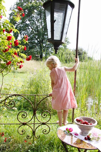 Little blond girl balancing on the railing of a garden pavilion