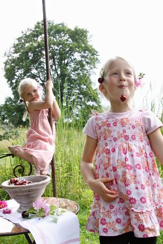 Two little blond girls eating cherries in a garden