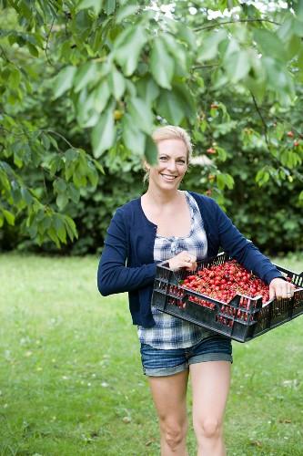 Woman carrying basket of cherries