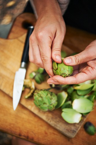 Woman's Hands Peeling Baby Artichokes Over a Wooden Cutting Board