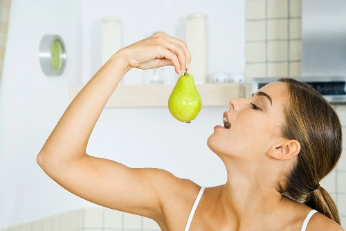 Woman holding up pear, head back, mouth open, side view