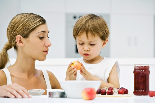 Mother and son preparing food together, boy holding apple, both looking down