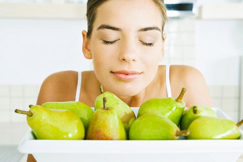 Young woman smelling fresh pears, eyes closed, close-up