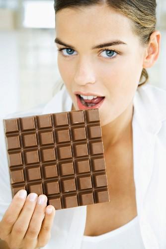 Woman biting into large chocolate bar, looking at camera