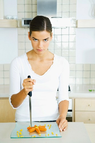 Young woman in kitchen with plate of carrot sticks, holding knife menacingly