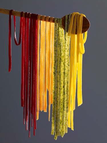 Home-made tagliatelle hanging on a wooden spoon