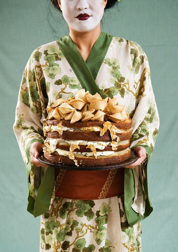 An Asian woman holding a celebration cake decorated with gold leaf and fortune cookies