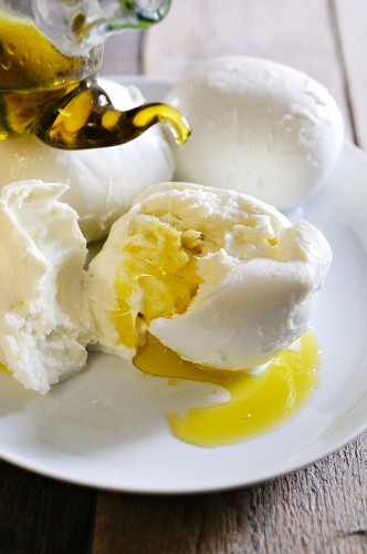 A ripped open ball of buffalo mozzarella being drizzled with extra virgin olive oil