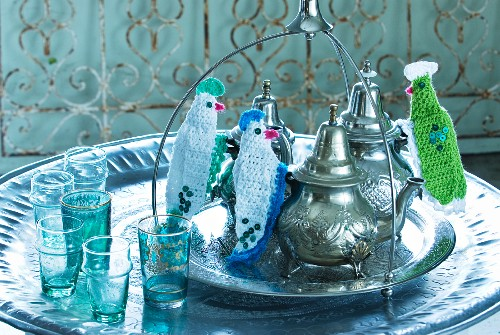 A round metal dish holding Oriental teapots with knitted finger protectors on the handles, with coloured tea glasses