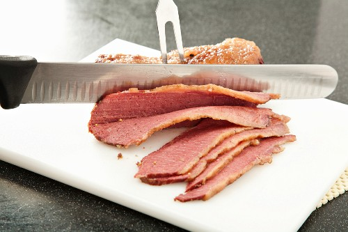 Slicing Corned Beef on a White Plastic Cutting Board