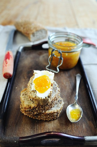 Slices of mixed seed brown bread topped with butter and homemade Clementine jam
