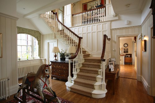 An antique rocking horse in front of a white-painted wooden staircase in the spacious hallway of a classy but comfortable country house with parquet flooring